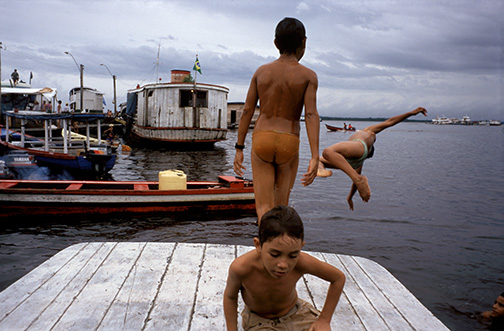 School boys in the Amazon port city of Manaus leap from fishing boats into the Rio Negro below a central city market. The Rio Negro enters the Rio Solimões at Manaus to form the Brazilian Amazon. School boys in the Amazon port city of Manaus leap from fishing boats into the Rio Negro below a central city market. The Rio Negro enters the Rio Solimões at Manaus to form the Brazilian Amazon. © Kevin Moloney, 1995