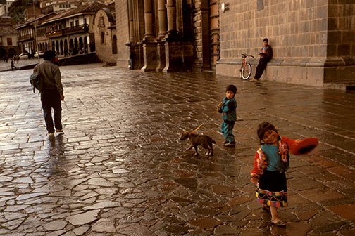 A young girl in traditional Indian dress dances through Cuzco's Plaza de las Armas as her brother hangs onto the family dog at rear. The kids were put on display for their mother to attract alms from passers-by. © Kevin Moloney, 1996.