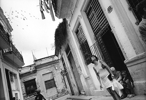 Pigeons fly overhead as a Havana resident looks up to gauge the day's weather. © Kevin Moloney, 2001.
