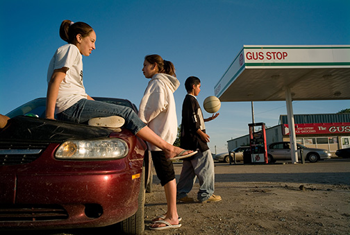 Teens Ariel Farmer, 14, left, Kyla Sharp Butte, 14, center, and Will Sharp Butte, 15, hang out on the hood of a car in the parking lot of a convenience store to pass time on the Rosebud Sioux Reservation in southern South Dakota, Thursday, May 24, 2007. An epidemic of teen suicides and attempts has reservation adults worried. Making these images caused a worried father — even one to whom I had introduced myself — call the tribal police. © Kevin Moloney, 2007.