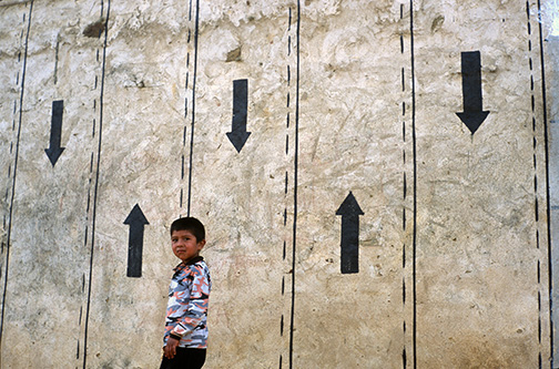 "A boy walks below artfully painted walls in the village of Pucará, Bolivia. Ernesto ""Che"" Guevara was captured by the Bolivian army in 1967 in a nearby valley and executed in nearby La Higuera days later. © Kevin Moloney, 2004."