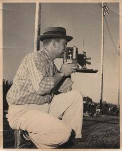 My father, Paul F. Moloney, photographs a Colorado State College (now University of Northern Colorado) football game from the sidelines of Jackson Field in Greeley, Colo., in the fall of 1957. He holds a Speed Graphic press camera. (Photo/Bob Waters)
